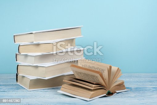 istock Book stacking. Open book, hardback books on wooden table and blue background. Back to school. Copy space for text 691467280