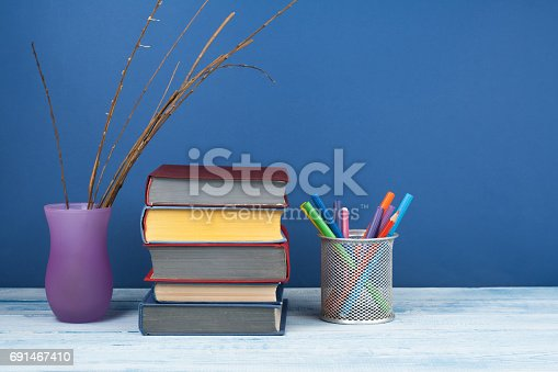 istock Book stacking. Open book, hardback books on wooden table and blue background. Back to school. Copy space for text 691467410