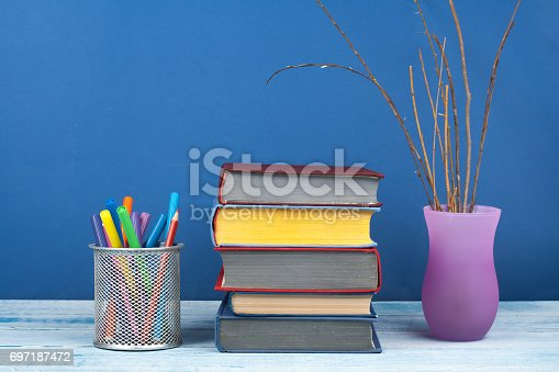 istock Book stacking. Open book, hardback books on wooden table and blue background. Back to school. Copy space for text 697187472