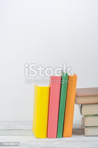 696860774 istock photo Book stacking. Open book, hardback books on wooden table and blue background. Back to school. Copy space for text 700268970