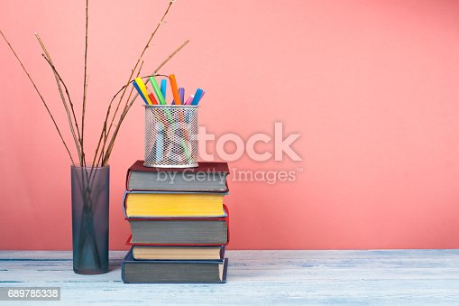 istock Book stacking. Open book, hardback books on wooden table and pink background. Back to school. Copy space for text 689785338