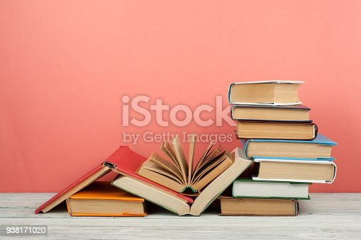 istock Book stacking. Open book, hardback books on wooden table and pink background. Back to school. Copy space for text 938171020