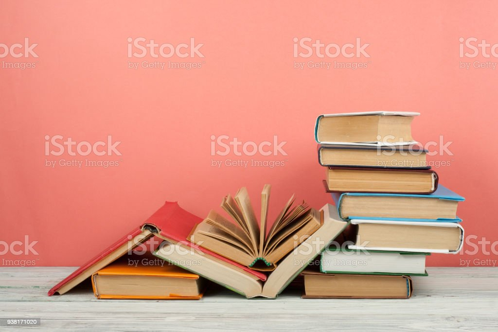 Book stacking. Open book, hardback books on wooden table and pink background. Back to school. Copy space for text stock photo