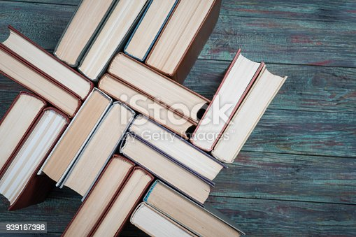 istock Book stacking open book hardback books on wooden table. 939167398
