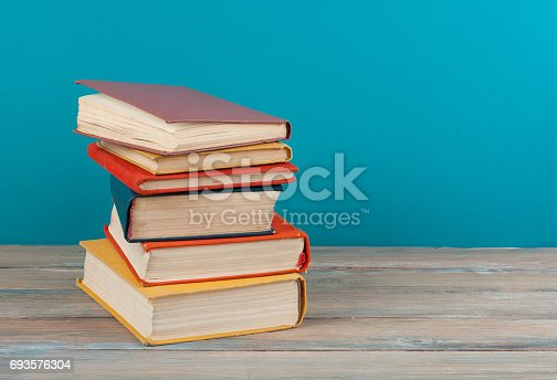 696860774 istock photo Book stacking. Open hardback books on wooden table and beige background. Back to school. Copy space for ad text 693576304
