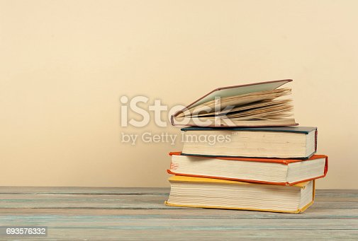 696860774 istock photo Book stacking. Open hardback books on wooden table and beige background. Back to school. Copy space for ad text 693576332