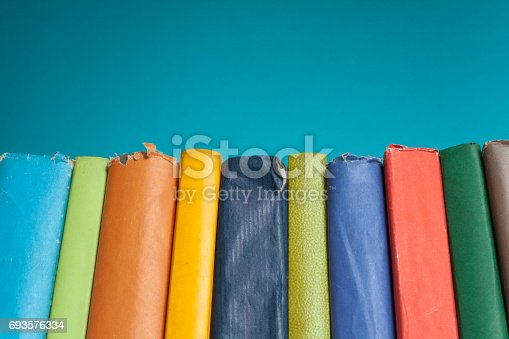 696860774 istock photo Book stacking. Open hardback books on wooden table and blue background. Back to school. Copy space for ad text 693576334