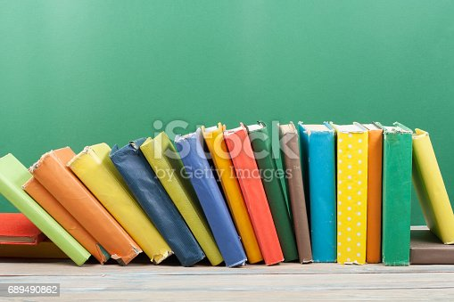 696860774 istock photo Book stacking. Open hardback books on wooden table and green background. Back to school. Copy space for ad text 689490862