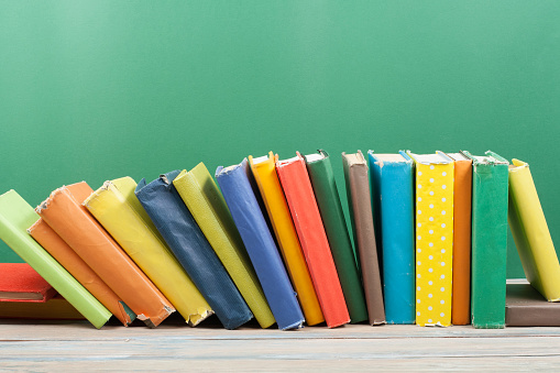 istock Book stacking. Open hardback books on wooden table and green background. Back to school. Copy space for ad text 689490862