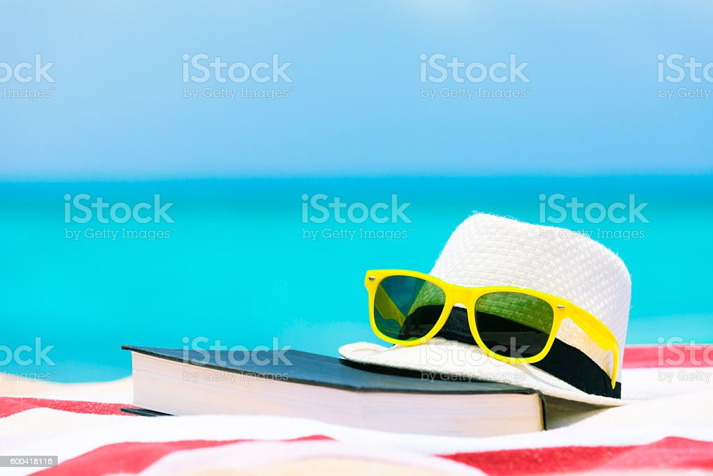 Book, sunglasses and hat on the beach. stock photo