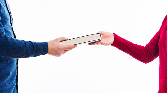 Close up portrait of man and women students exchanging books isolated on white. Literature sharing between people. Give to read to a friend as present. Person borrow textbook, swap of knowledge.