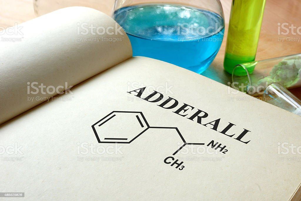 Book with adderall and test tubes on a table. stock photo
