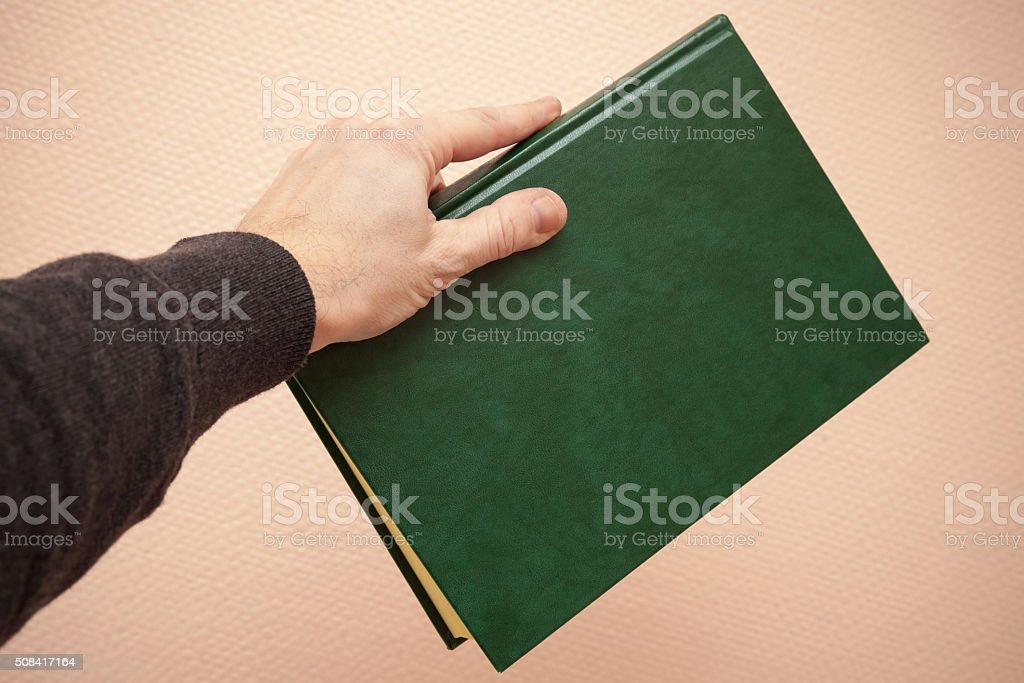 Book with empty dark green cover in male hand foto