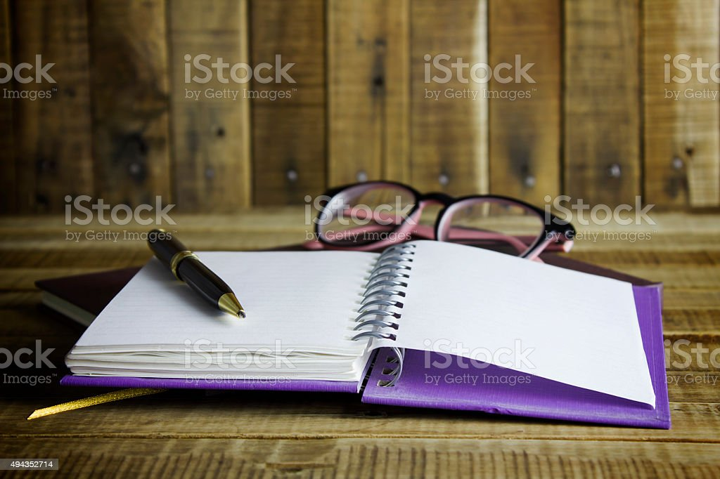 book with glasses and pen on the wooden background. stock photo