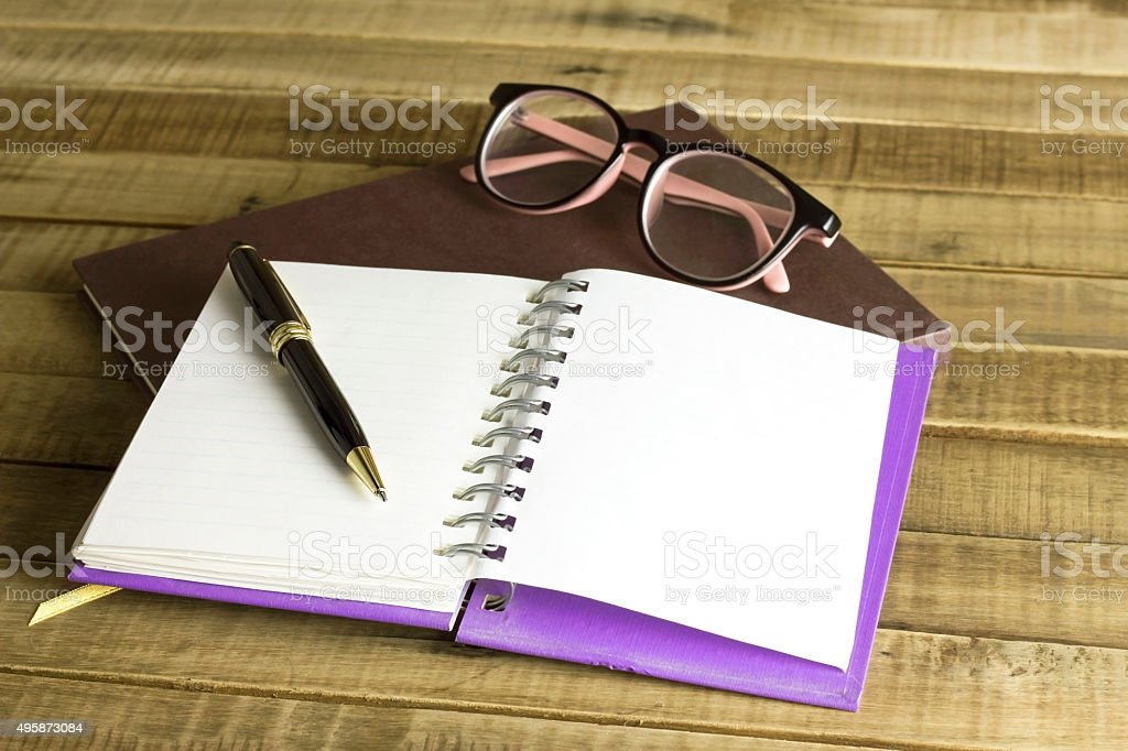 book with glasses and pen on the wooden background stock photo