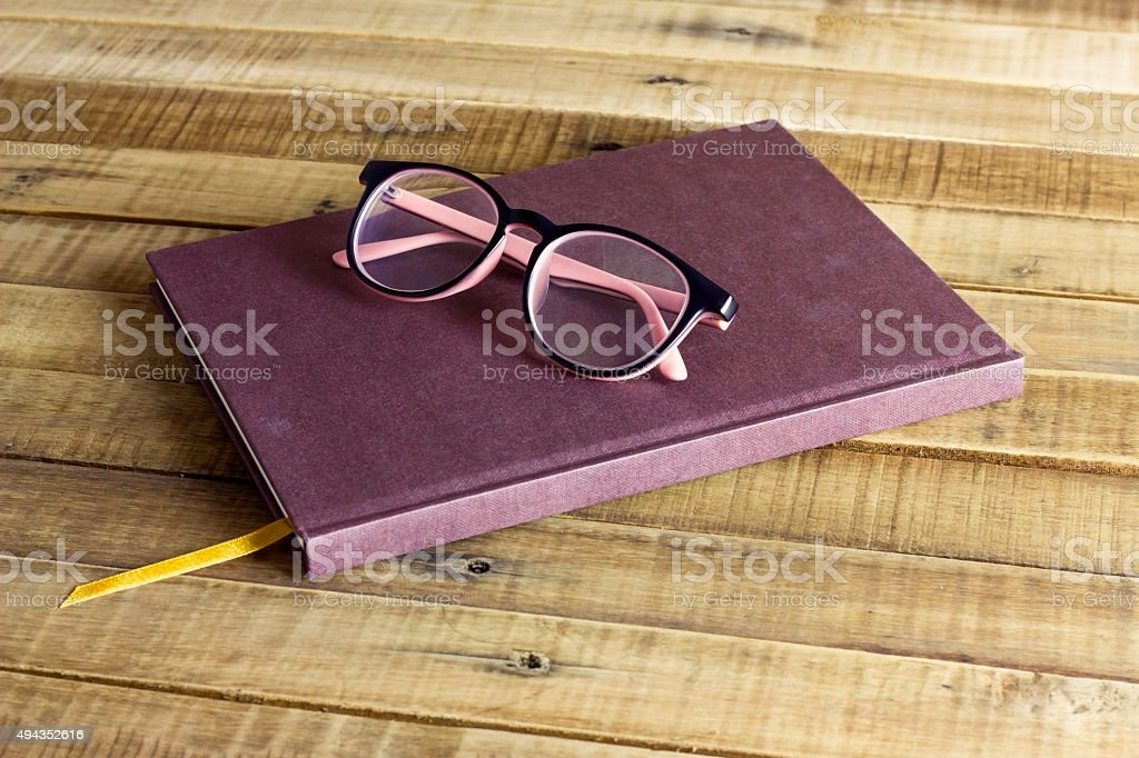 book with glasses  on the wooden background stock photo