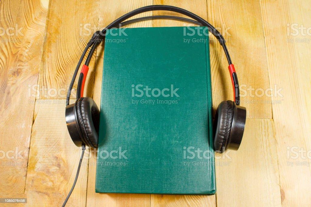 livro com fones de ouvido, conceito, audiobook - foto de acervo