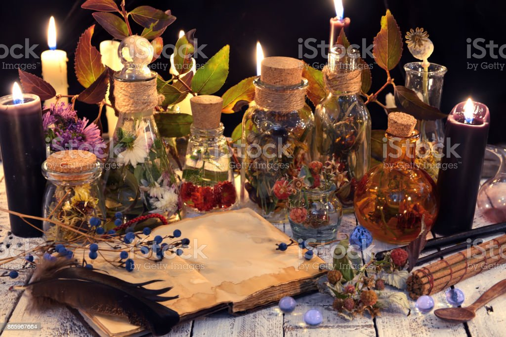 Book with herbs and berries, black candle and magic objects stock photo
