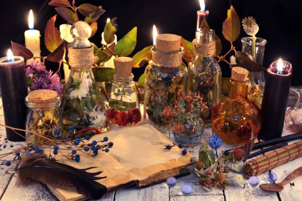 book with herbs and berries, black candle and magic objects - традиционная церемония стоковые фото и изображения