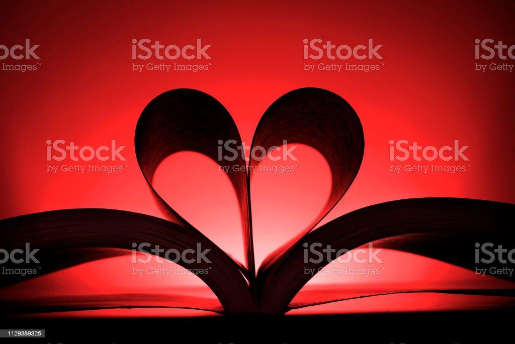 Buchen Sie mit Seiten verwandelte sich in die Form einer Herz Liebe roten Hintergrund zu lesen – Foto