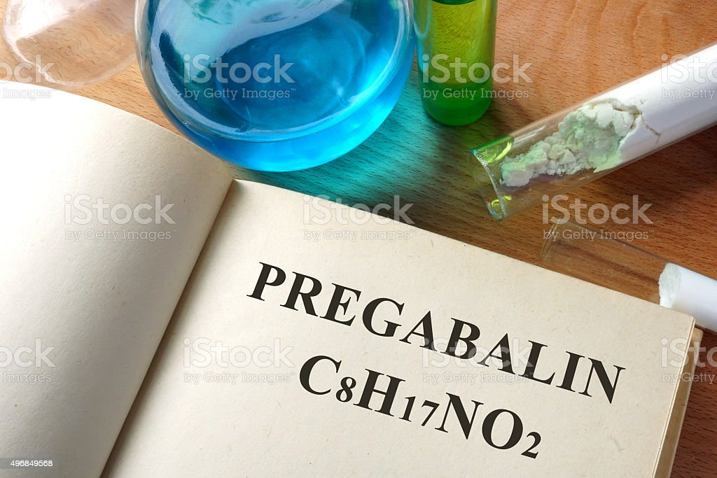 Book with Pregabalin  and test tubes on a table. stock photo