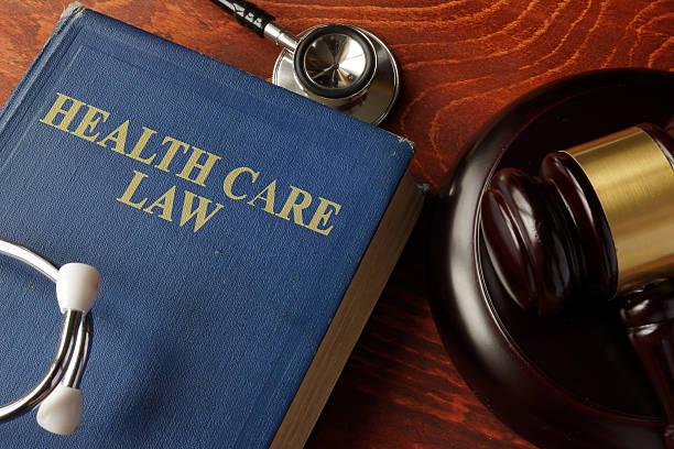 book with title health care law on a table. - legislación fotografías e imágenes de stock