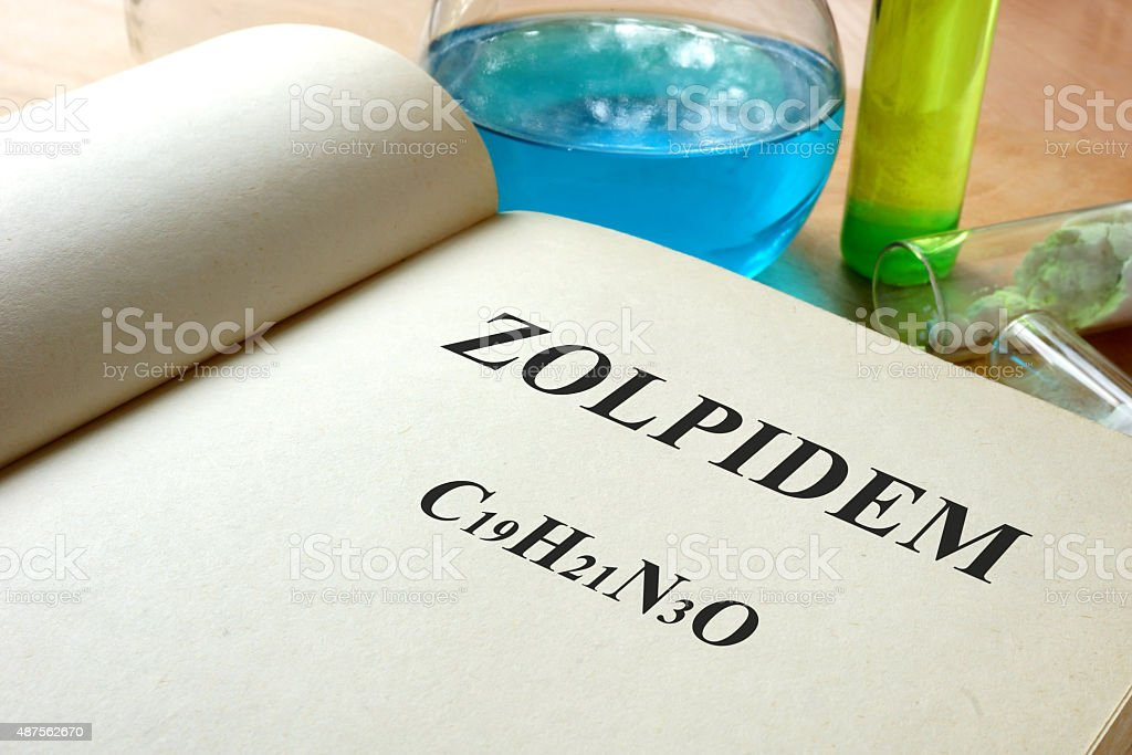 Book with Zolpidem and test tubes on a table. stock photo