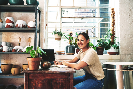 Cropped portrait of an attractive young business owner sitting alone in her pottery studio and making notes