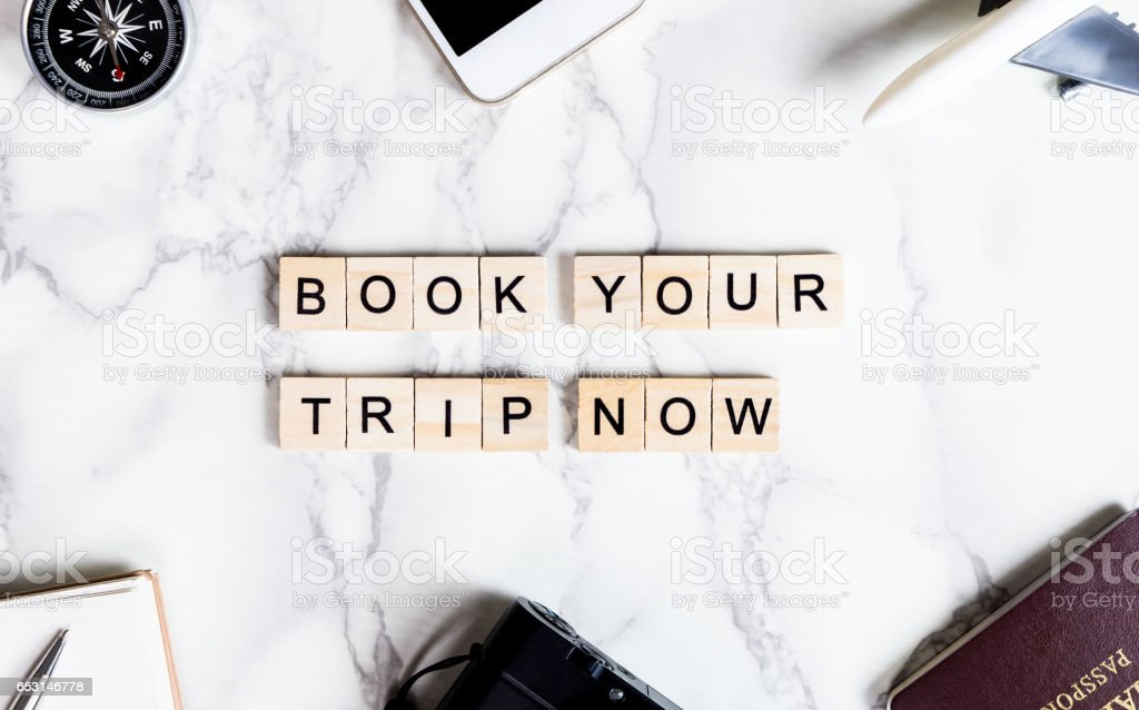 Book your trip now text on marble table with travel accessories stock photo