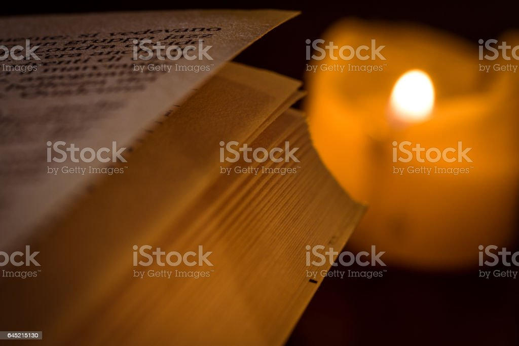 book_by_candlelight stock photo