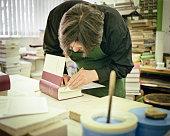 bookbinder in his workshop restores an antique book