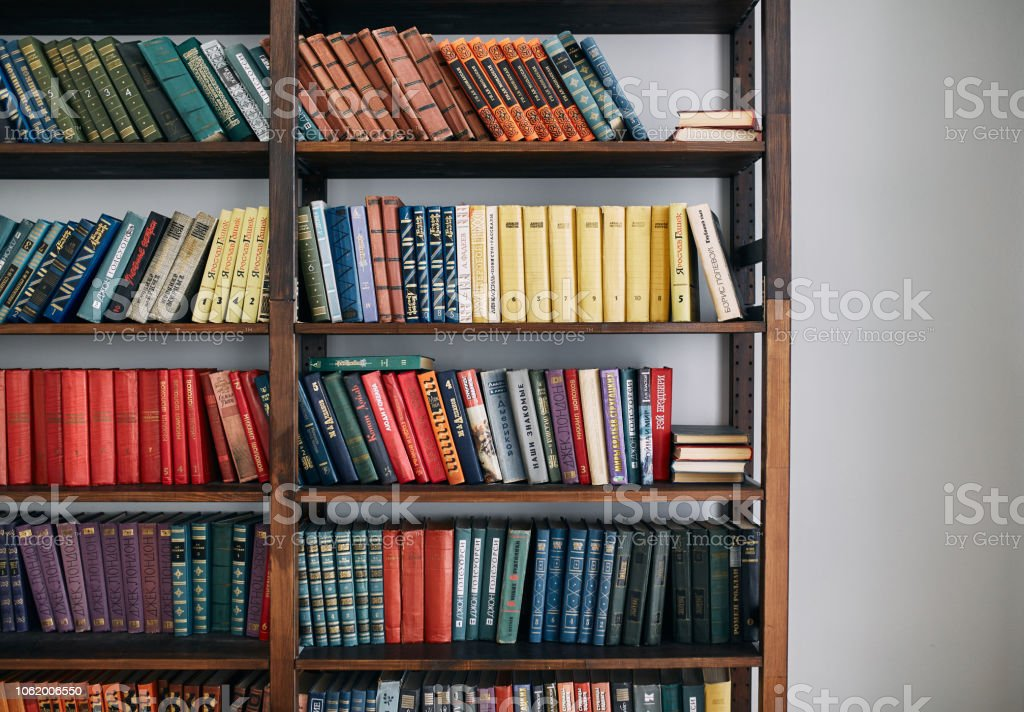 Bookcase with old books on the shelves. Books in an old wooden Cabinet