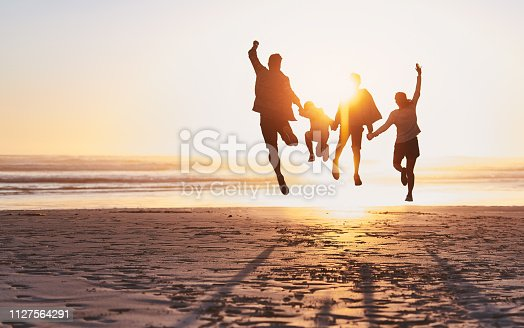 Rearview shot of a happy young family jumping for joy at the beach