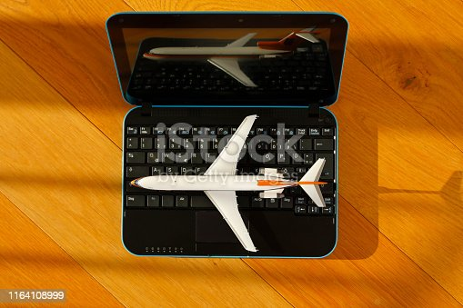 Booking a flight with a model airplane and a laptop on a wooden floor