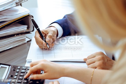 istock Bookkeeper or financial inspector and secretary making report, calculating or checking balance. Internal Revenue Service inspector checking financial document. Audit concept. 1159979474