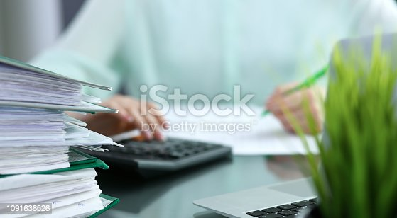 istock Bookkeeper or financial inspector  making report, calculating or checking balance. Audit and tax service concept. Green colored image background. 1091636526