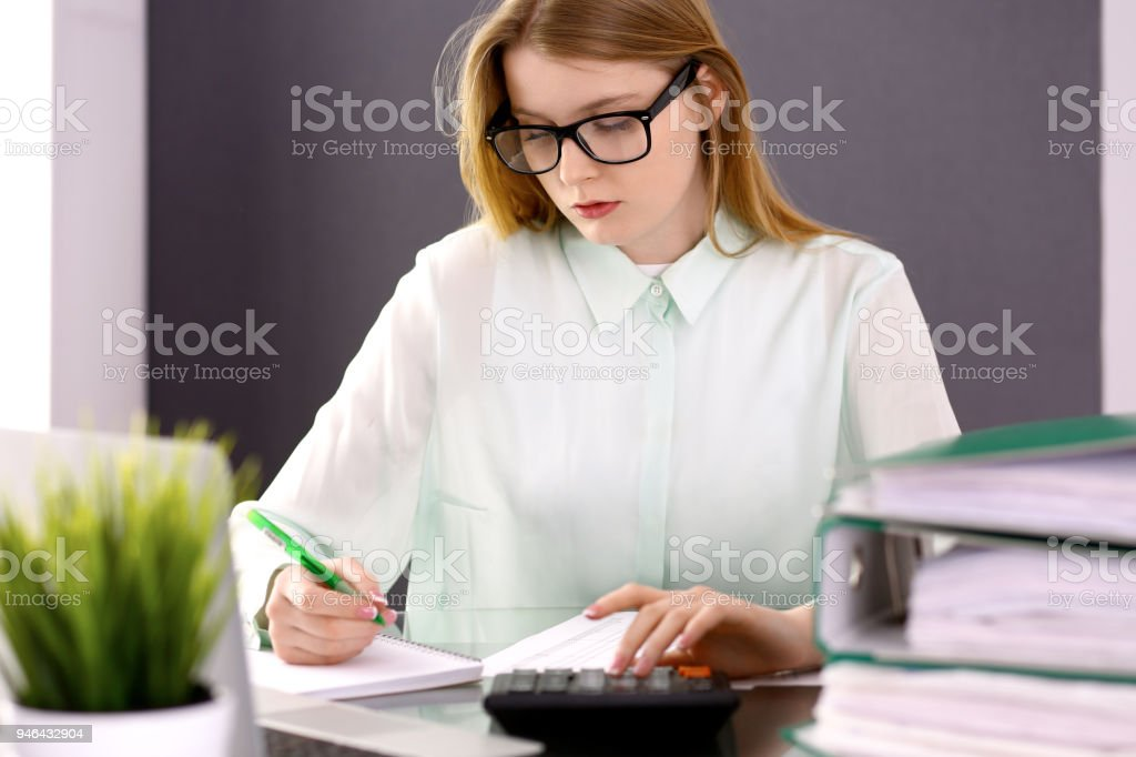 Bookkeeper or financial inspector  making report, calculating or checking balance. Audit and tax service concept. Green colored image backgroun stock photo