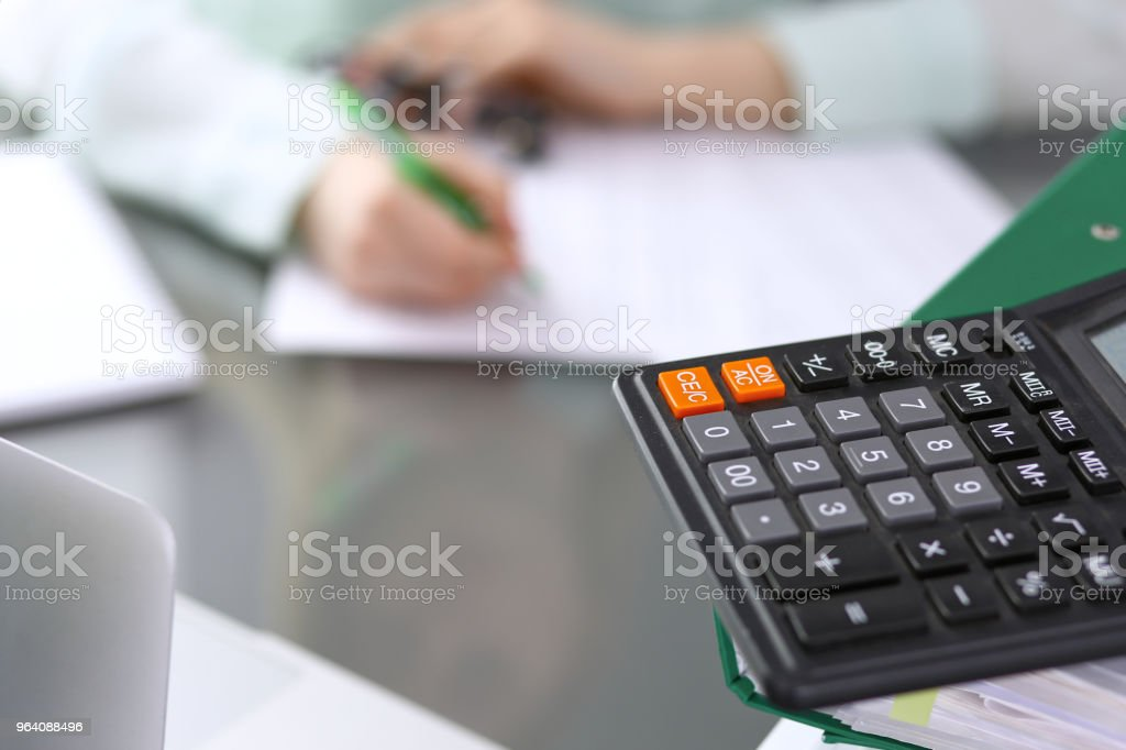Bookkeeper or financial inspector  making report, calculating or checking balance. Binders with papers closeup. Audit and tax service concept. Green colored image backgroun - Royalty-free Accountancy Stock Photo