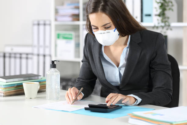 Bookkeeper with mask calculating with calculator stock photo