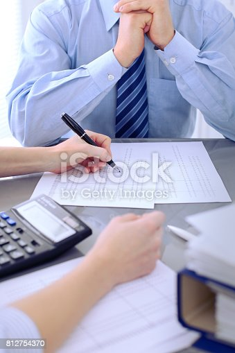 istock Bookkeepers or financial inspector making report, calculating or checking balance. Audit concept. 812754370