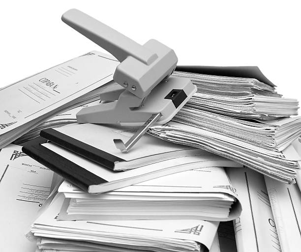 book-keeping documents and puncher these are a stack of book-keeping documents and a big puncher append stock pictures, royalty-free photos & images