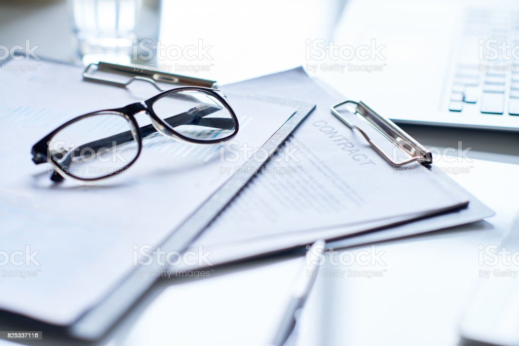 Bookkeeping Close-up of clipboards with business papers and eyeglasses Agreement Stock Photo
