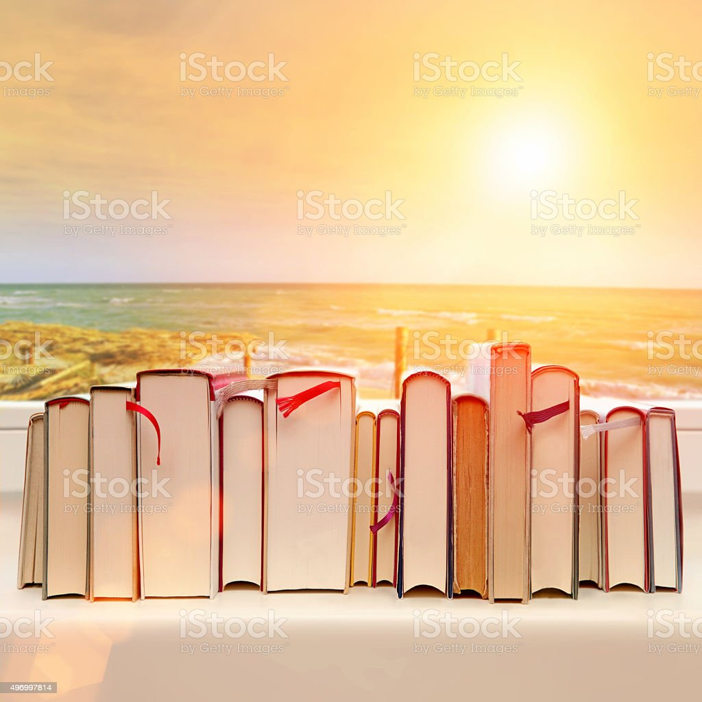 Books aligned on window sill with a seaside sunset background stock photo