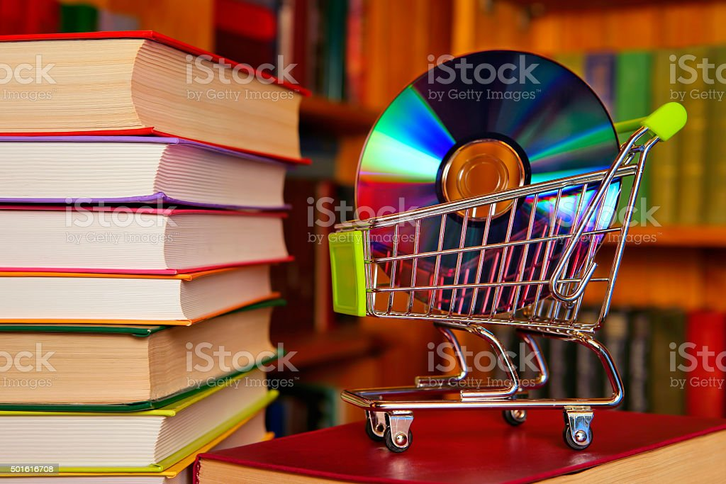 Books and a shopping cart with a Compact Disc stock photo