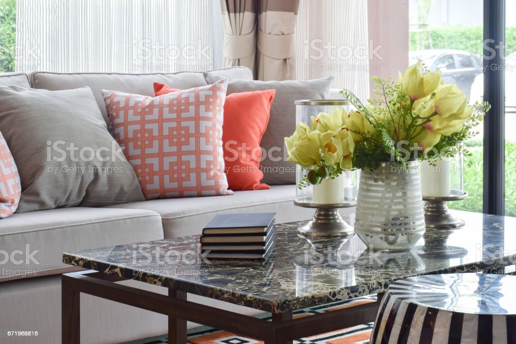 Books and decorative items on marble top table and lively sofa set stock photo