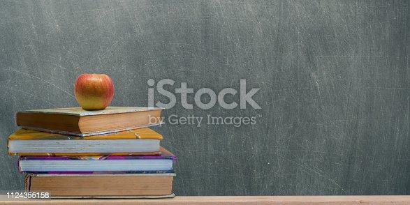 istock books and fresh apple against chalkboard. 1124355158