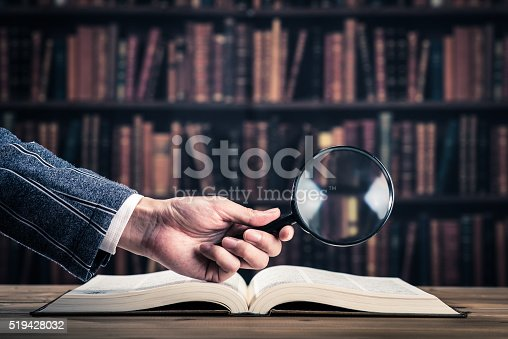 istock Books and magnifying glass 519428032