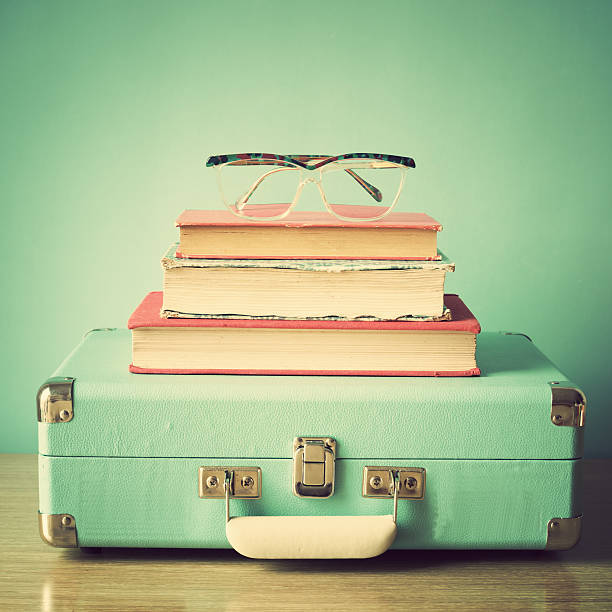 Books and suitcase stock photo