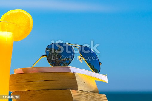 istock Books and sunglasses on a beach 516398258