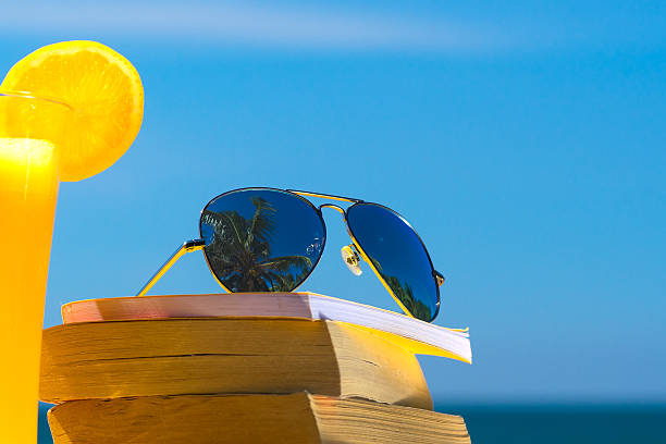Books and sunglasses on a beach stock photo